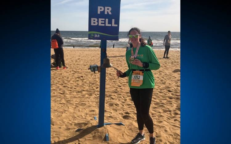 Torie Smith rings the bell for a personal best time at the Shamrock Half Marathon at Virginia Beach. Submitted photo.