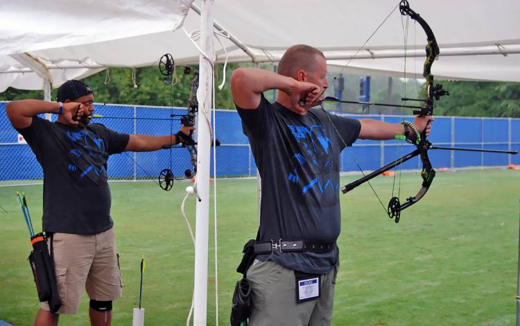 Army veterans Anthony Jackman, left, and Brian Miller, right, compete in archery at Valor Games Southeast.