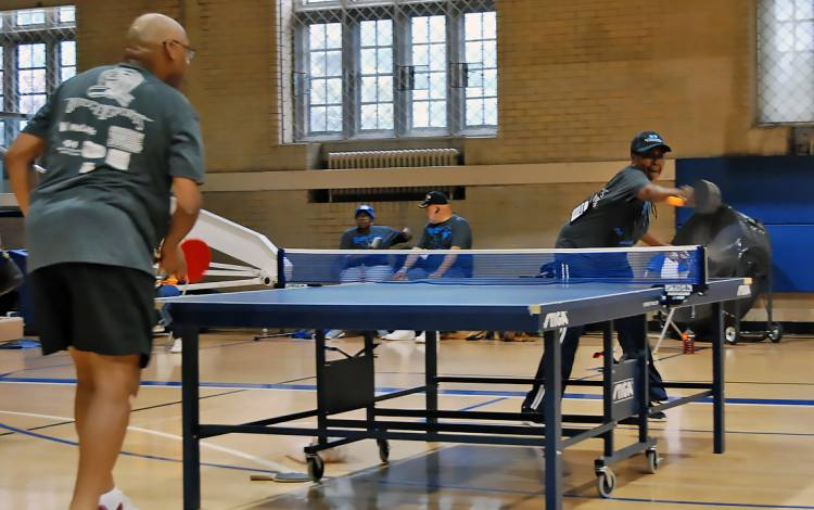 Teresa Brown, right, returns a shot by Daniel Harris, left, in their table tennis match.