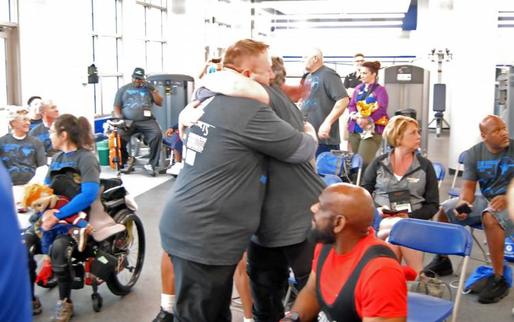 Army veteran Paul Belk, left, hugs Navy veteran Claudia Barber-Martin after she bench pressed 100 pounds.