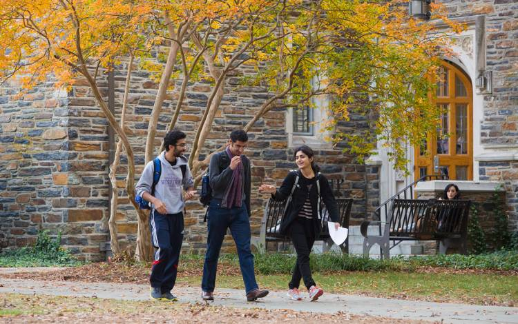 Students walk in front of West Campus buildings constructed of Duke stone.