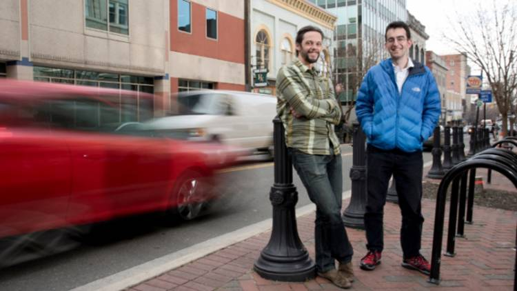 Efe Aras stands with his adviser Galen Reeves in the busy streets of downtown Durham. Their research aims to reveal how much traffic might change if cars could go park themselves