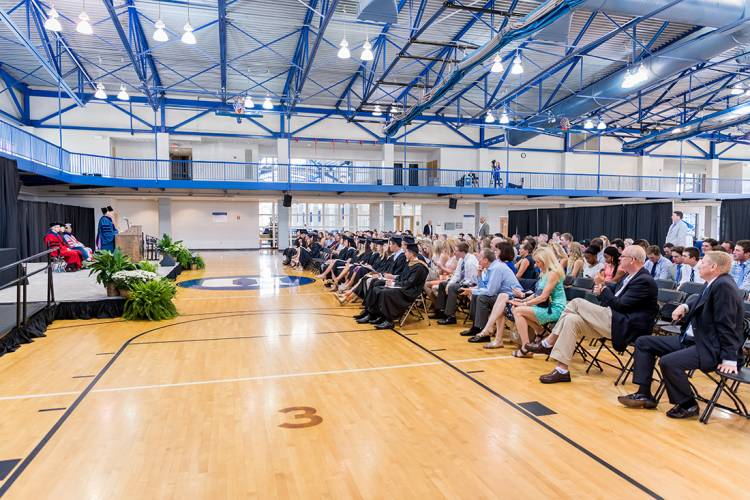 Student-athletes, family members and friends listen at a special graduation ceremony Monday.