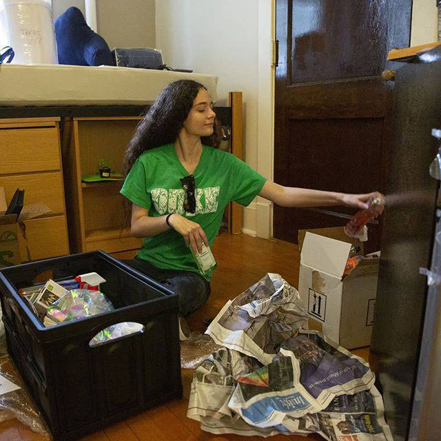 young student sorts out her possessions in her dorm room