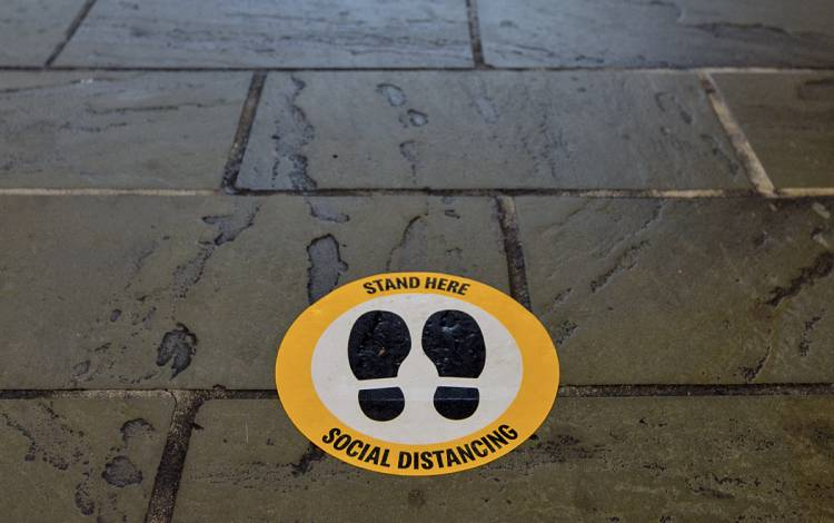 A decal showing how to social distance.