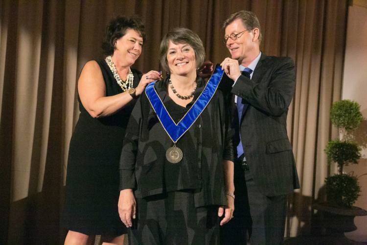 Alumni director Sterly Wilder and President Vince Price award former nursing dean Catherine Gilliss the University Medal.