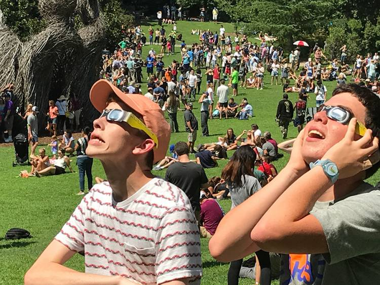 Zack Hersh, 16, of Chapel Hill and Oliver Egger, 16, of Durham watch the eclipse through their glasses.  Photo by Keith Lawrence.