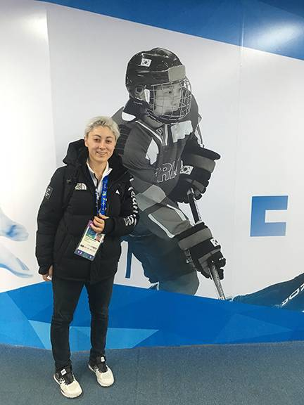 Duke Olympian Randi Griffin poses at the Team Korea House inside Gangneung Olympic Park in front of a poster of one of her teammates, Danelle Im. Photo courtesy of the Korean Ice Hockey Association.