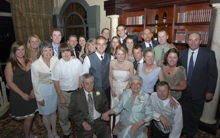 Laura and Josh Howes, center, surrounded by family at their wedding.