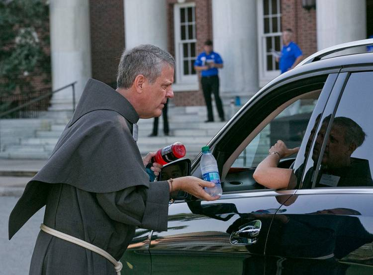 For the eighth year running, Father Mike Martin of the Duke Catholic Center handed out water to parents and students. Photo by Megan Mendenhall.