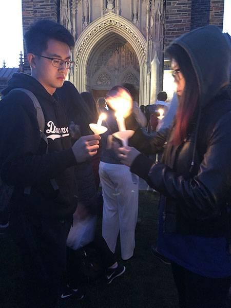 Two students light candles at vigil