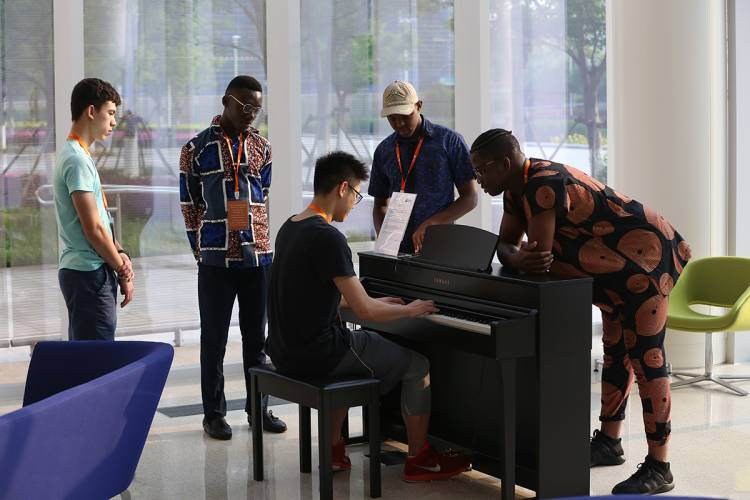 Duke Kunshan University students gather around a piano in a campus common area.