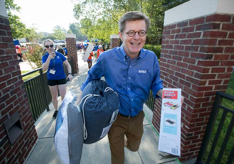 President Vince Price carries a student's belongings into a residence hall Tuesday. Photo by Jared Lazarus/Duke Photography