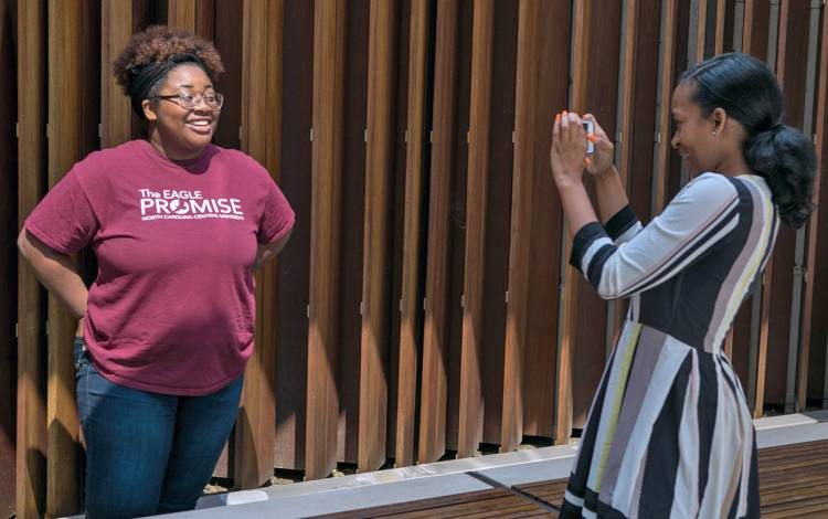 NCCU interns Palace Jones, left, poses for a photo for Maya O'Neal during a photography workshop at the Brodhead Center. Photo by Jonathan Black.