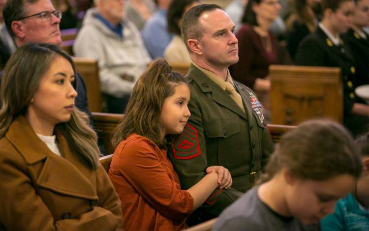 Flanked by his wife Sindy, left, and his daughter Isabella, center, Gunnery Sgt. Robert Weinhardt watches Monday's ceremony. Photo by Jared Lazarus.