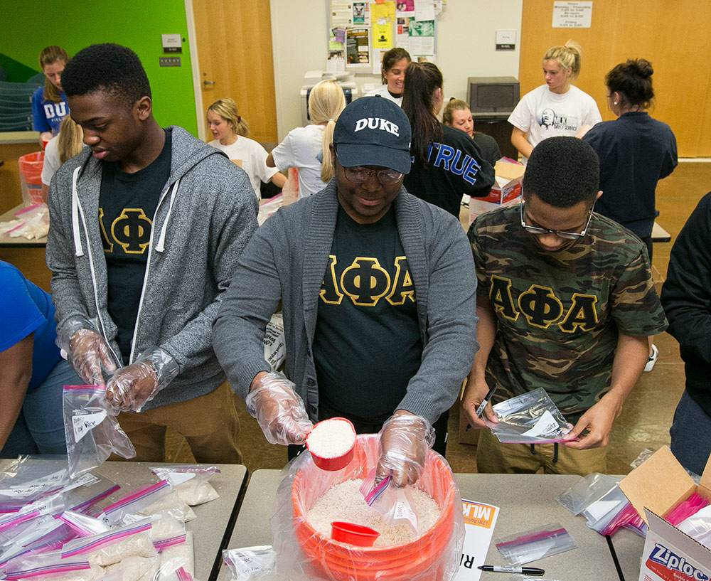 unde Abu, Serges Himbaza, and Lee Barnes, senior members of the Alpha Phi Alpha fraternity, along with other Duke community members commemorate the MLK holiday during a meal-packing event at Durham Tech. Photos by Megan Mendenhall/Duke Photography