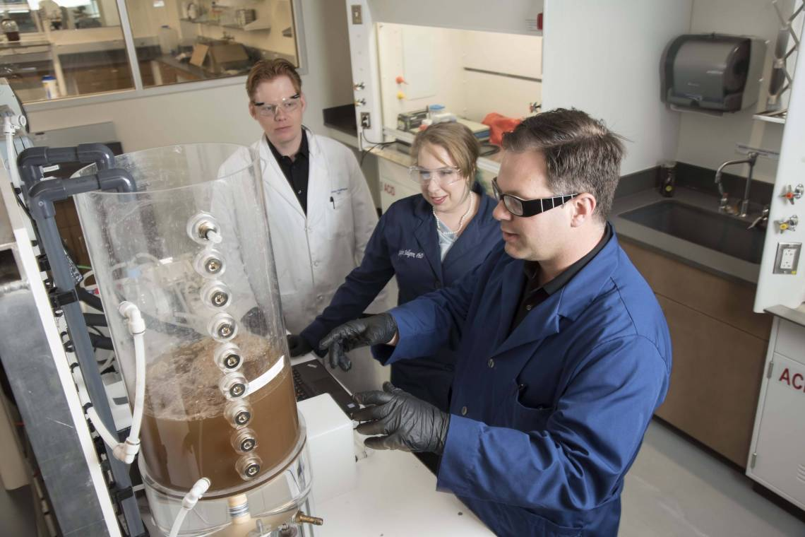 Researchers Brian Hawkins, Katelyn Sellgren, and James Thostenson work together at the Center for WaSH-AID housed in Duke's Chesterfield Building lab space