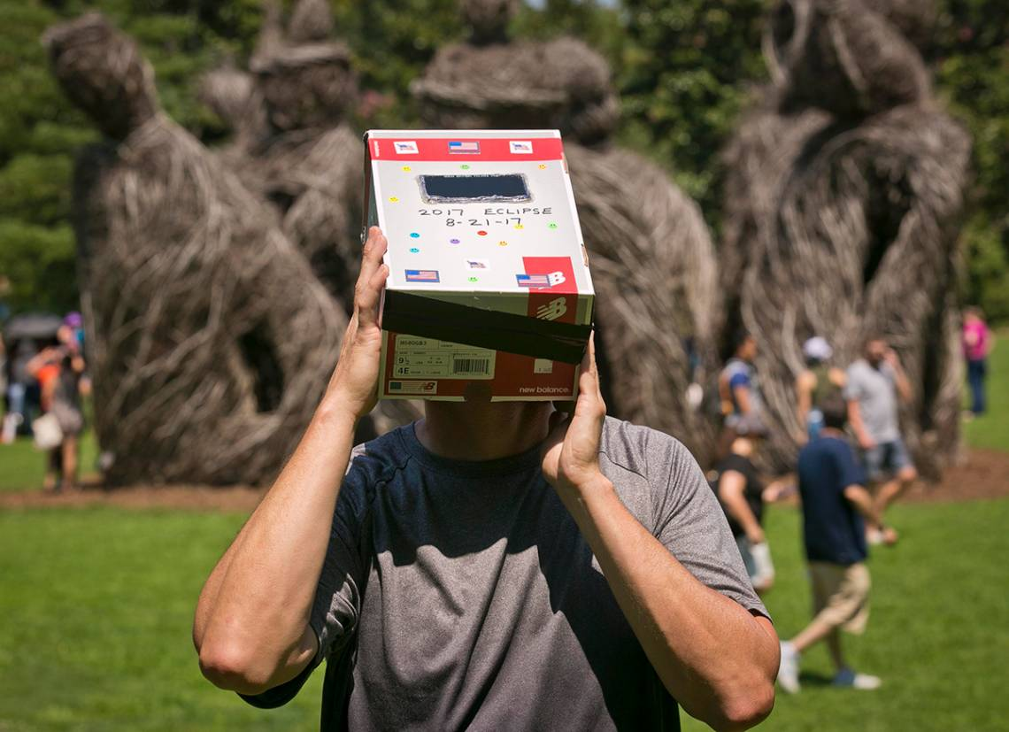 Wayne Little uses a homemade device made of welders glass and a cardboard box to watch the eclipse in Duke Gardens. Photo by Megan Mendenhall/Duke Photography