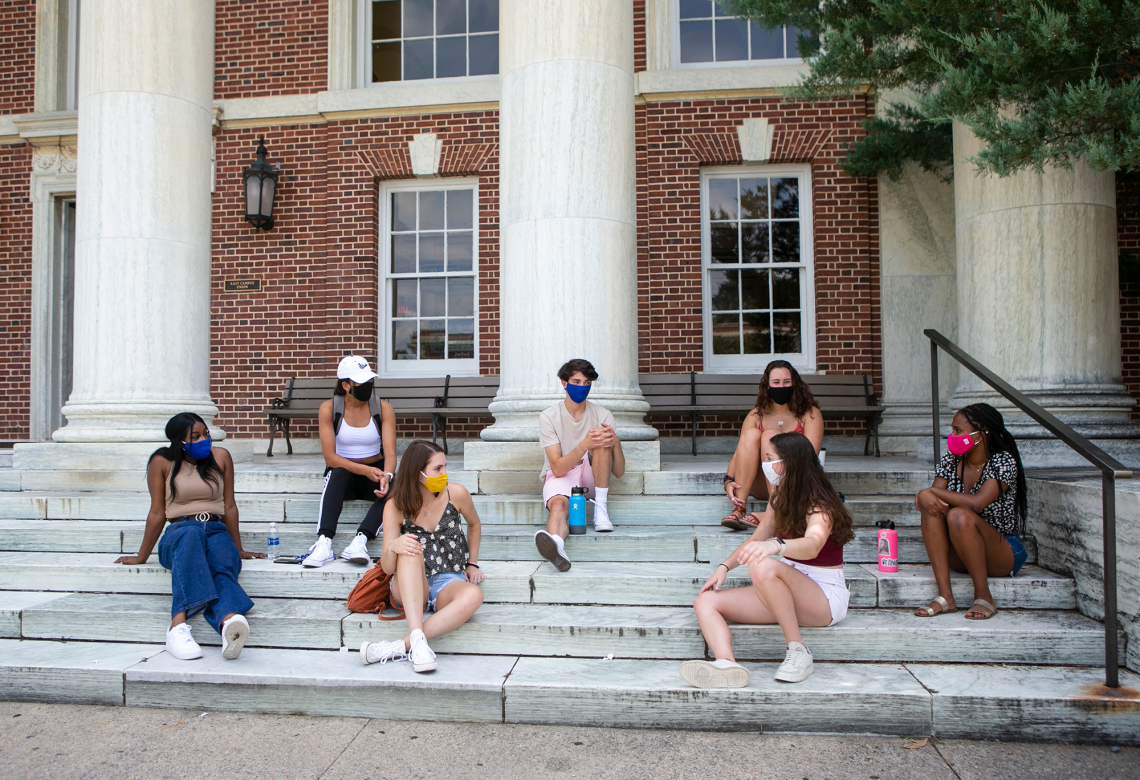 Residential students sit on the steps of East Union on East Campus. Student voices played a valuable role in reconfiguring campus housing for the pandemic.