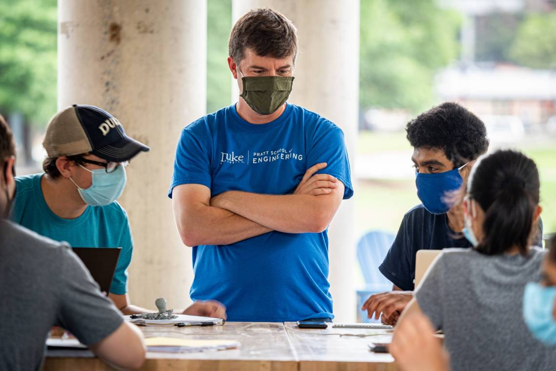 Instructor Ben Cooke teaches students in Engineering 101 outside