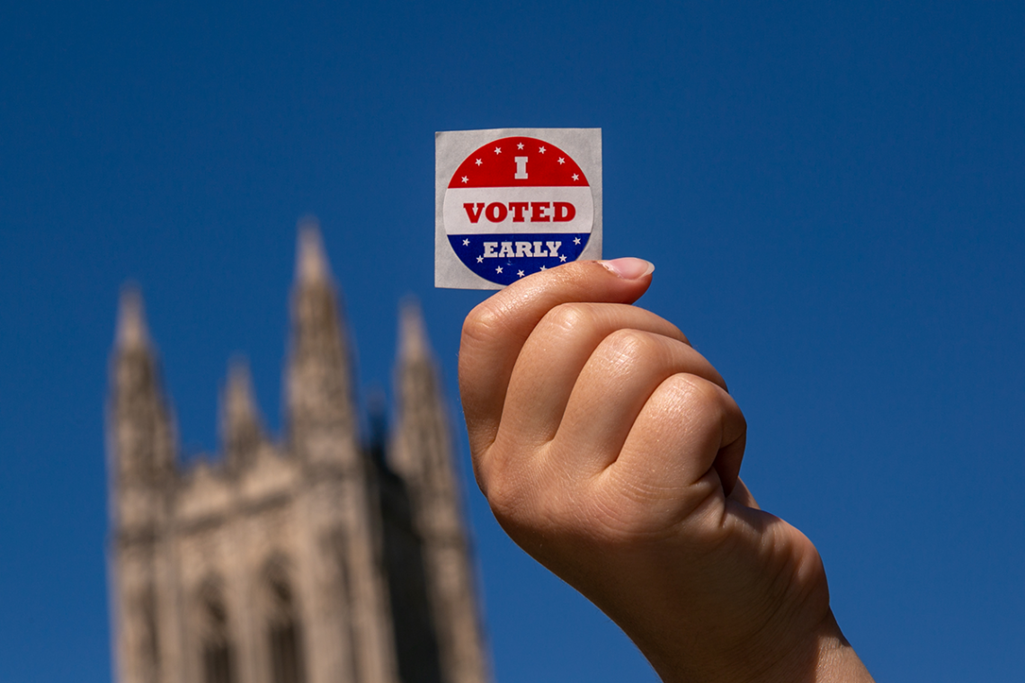 Duke student shows I Voted sticker on Duke's campus