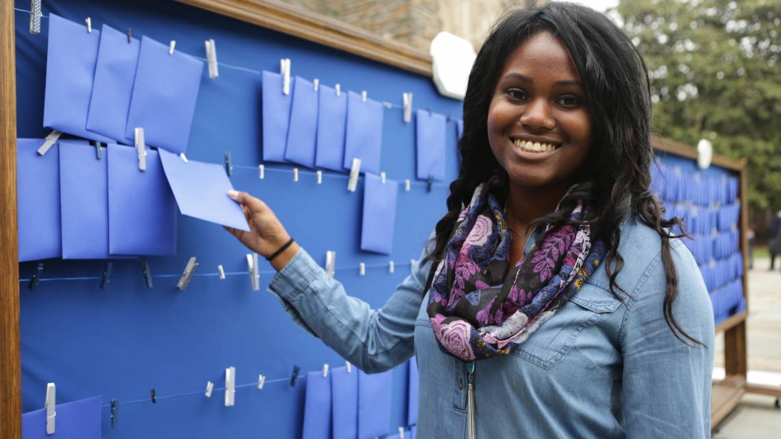 A Duke graduating senior selects a note written by alumni on a wall of advice the Duke Alumni Association provided on May 12.
