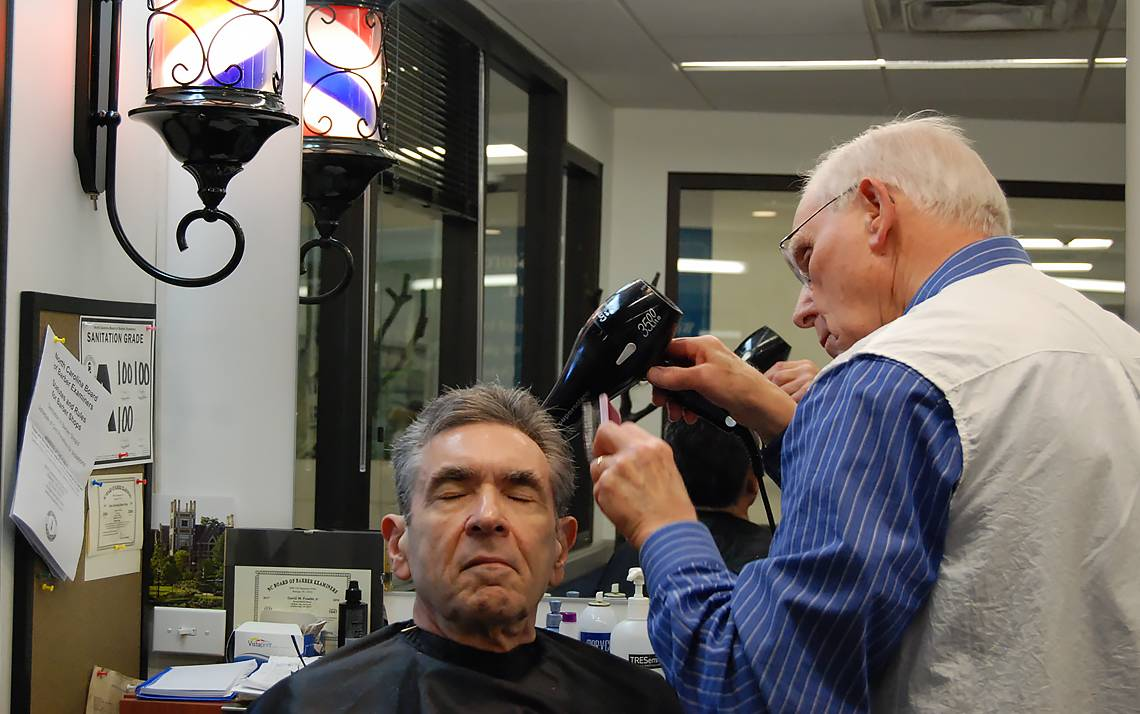 Duke Barber Shop fixture Dave Fowler cuts the hair of Robert Lefkowitz, Duke University School of Medicine professor and Nobel Prize winner.