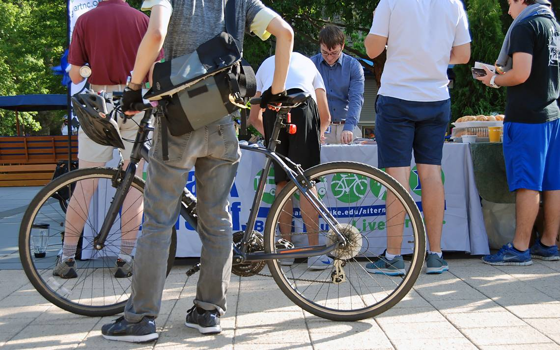 Cyclists look over free bike gear and information at Friday's Bicyclist Appreciation Breakfast at Bryan Center Plaza.
