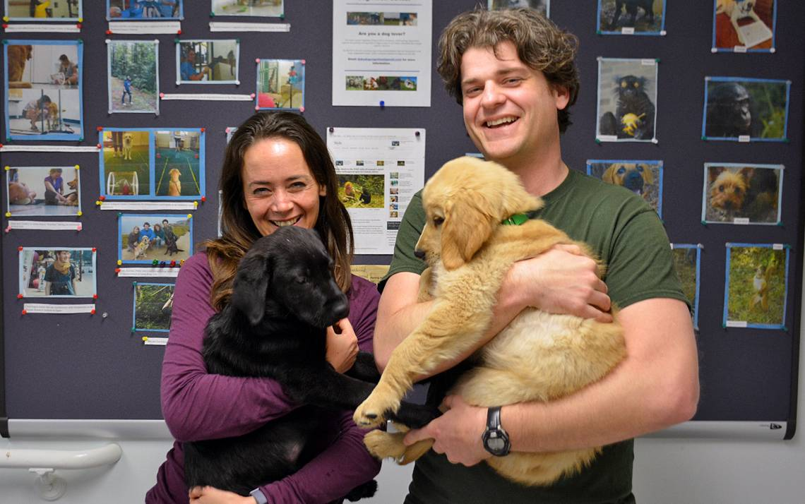 Vanessa Woods, left, holds Ernie while Brian Hare carries Kyler. The two puppies are being trained to become assistance dogs.