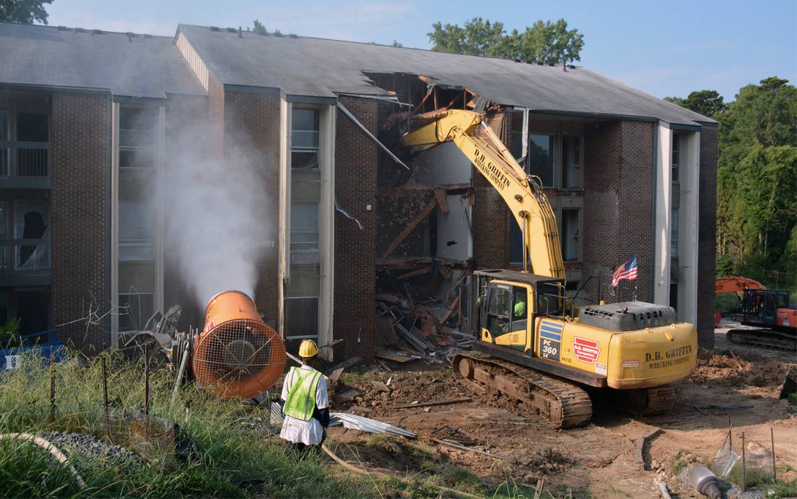Water sprays onto a former Central Campus apartment to reduce dust during building removal. Crews began demolishing buildings on Central Campus during the morning of Aug. 13. Photo by Jonathan Black.