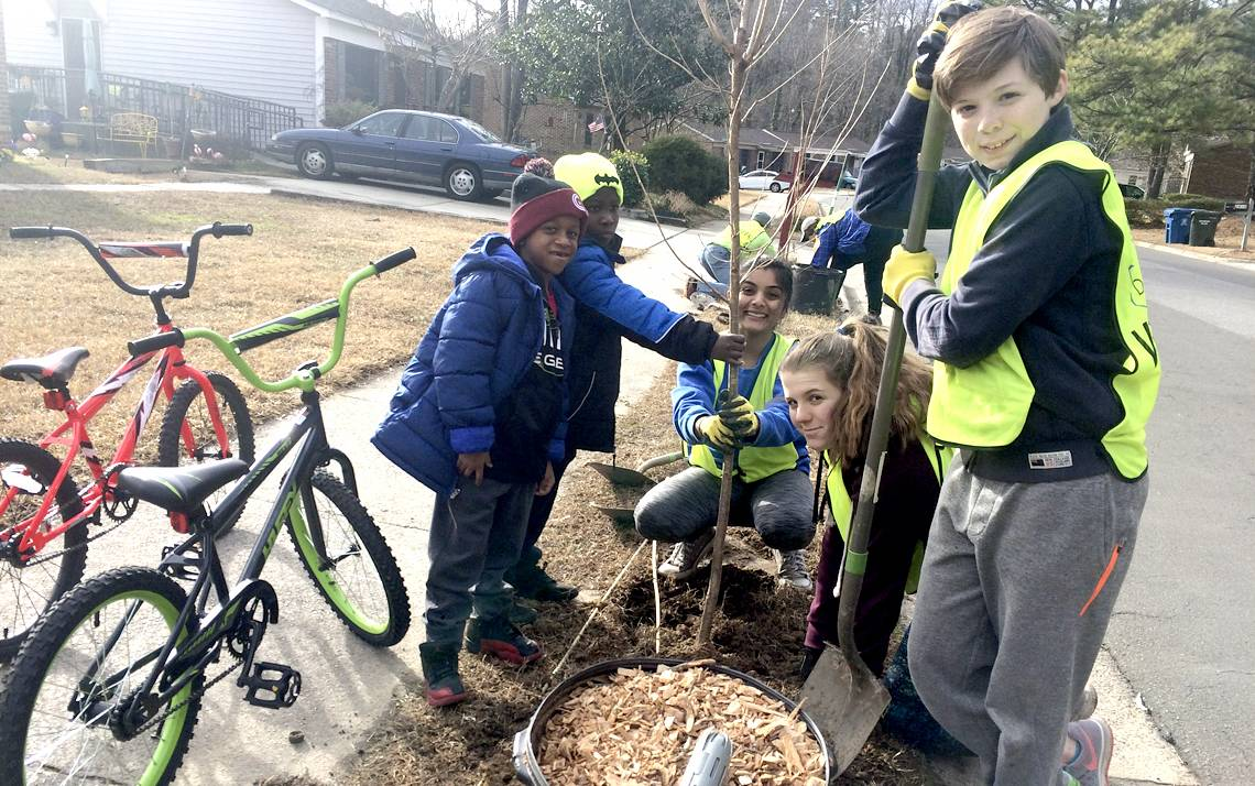 Duke student Tamanna Srivastava, center, plants a tree with the help of Keep Durham Beautiful volunteers and children from Durham's Northbrook neighborhood.