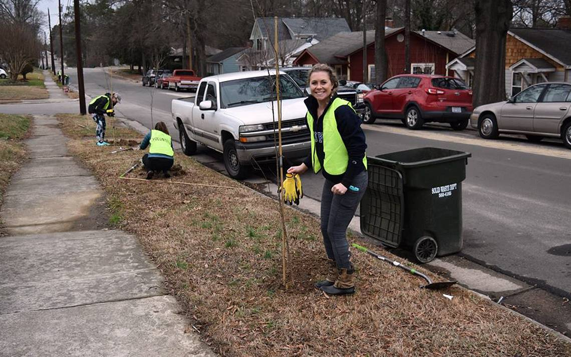 Duke Hospital nurse Ali Homan smiles as she plants trees in Durham's Walltown neighborhood.