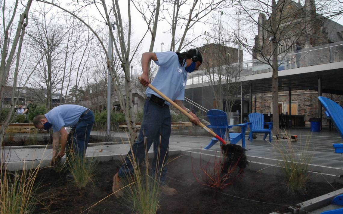 Steam rises from the mulch spread by Duke Facilities Management's Chadrick Rochelle while working on a project at Crown Commons. Photo by Stephen Schramm.