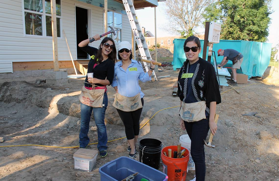 From left, Duke alumni Daniela Tort, Pranisa Ekachote and Vanessa Uriarte, volunteer with Habitat for Humanity in Durham in 2014 as part of the Rotary Center's commemoration of the International Day of Peace.