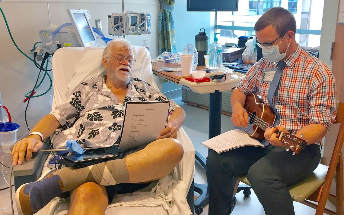 William Dawson, right, of Arts & Health at Duke, plays a ukulele for Duke University Hospital patient David Stucker. Photo courtesy of David Stucker's family.