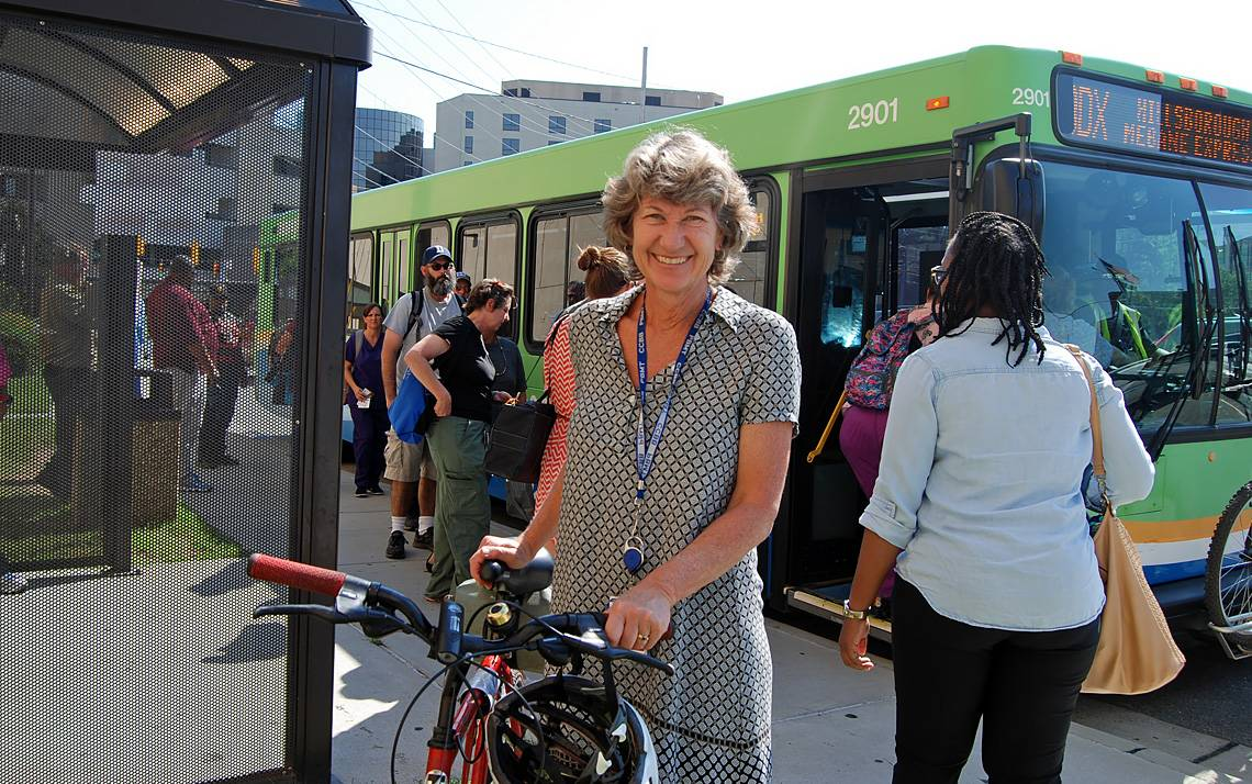 Deborah Wood with bike near a bus.