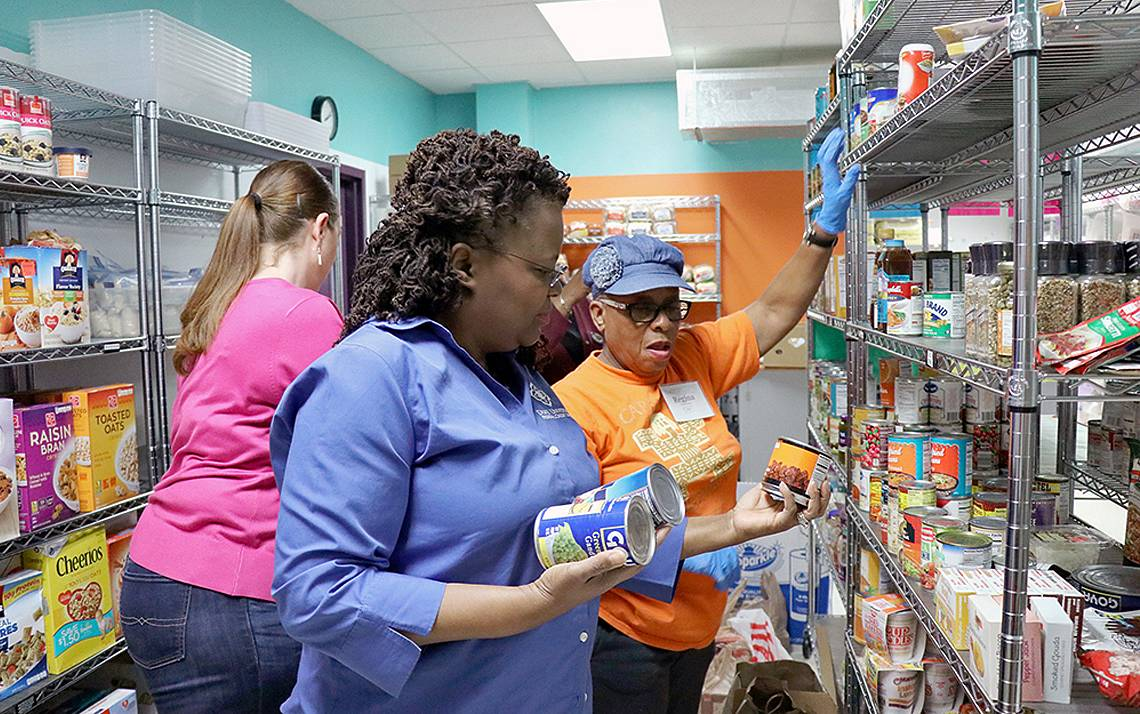 Duke Credit Union staff stock the shelves of Urban Ministries of Durham with food and amenities collected during  their March donation drive. Photo by James Hardman-Cobb.