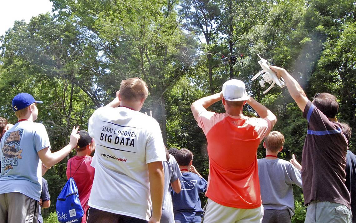 Kids watch a drone fly in Duke Forest.