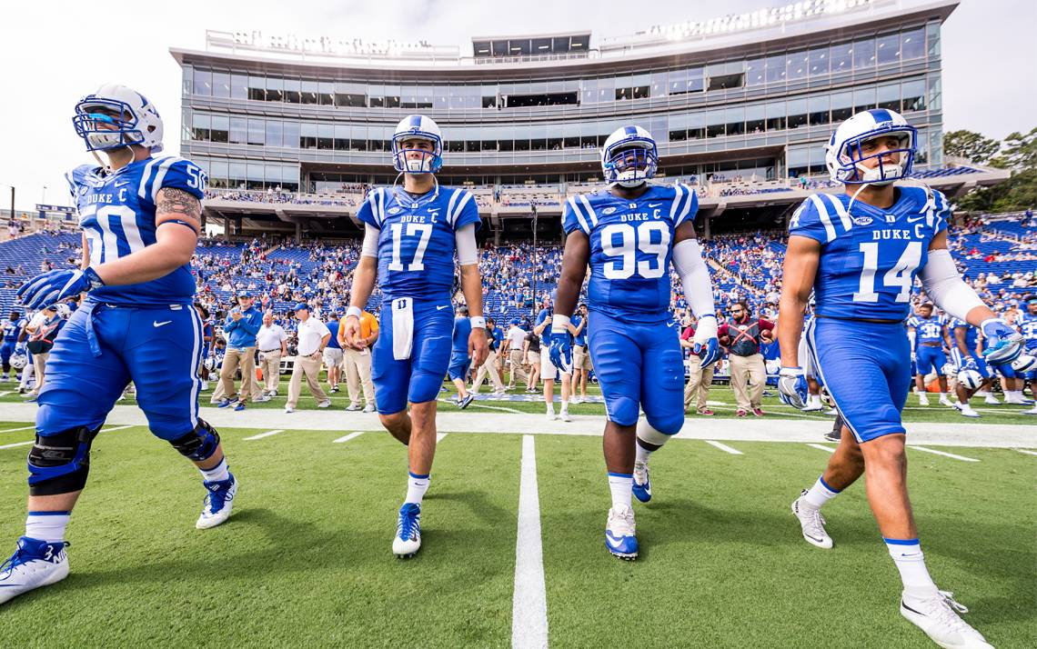 Duke Football players head to the coin toss.