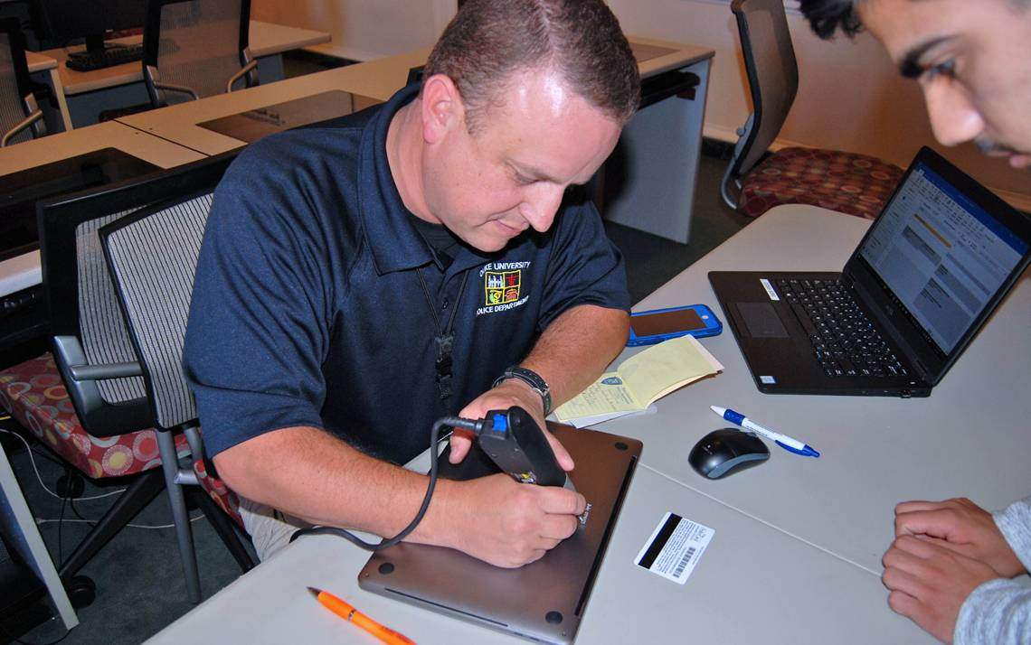 Duke Police Community Services Officer Kelly George engraves a student's laptop.