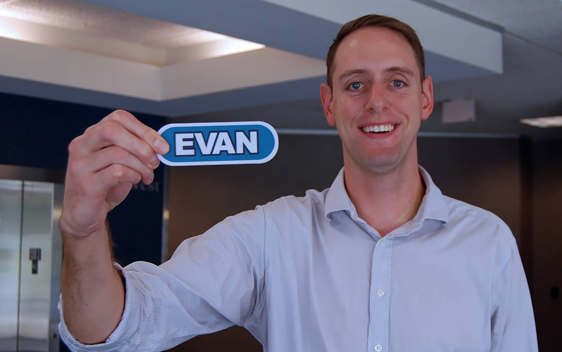 PRMO Financial Analyst Evan Schroedel holds the name tag from his appearance on Wheel of Fortune.