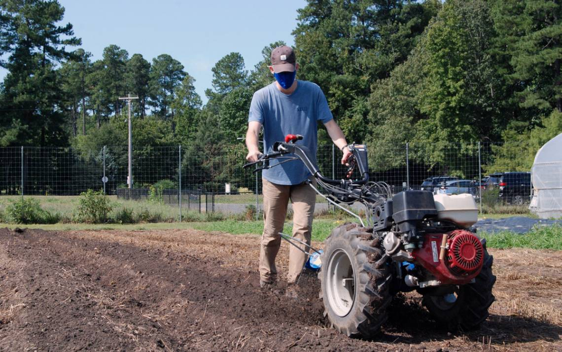 Graduate student Garrett Corwin tills the soil at Duke Campus Farm. Photo by Stephen Schramm.