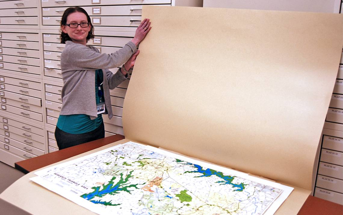 Duke University Archives Records Manager Hillary Gatlin shows off a map of Duke Forest recently transferred to the archives. Photo by Stephen Schramm.
