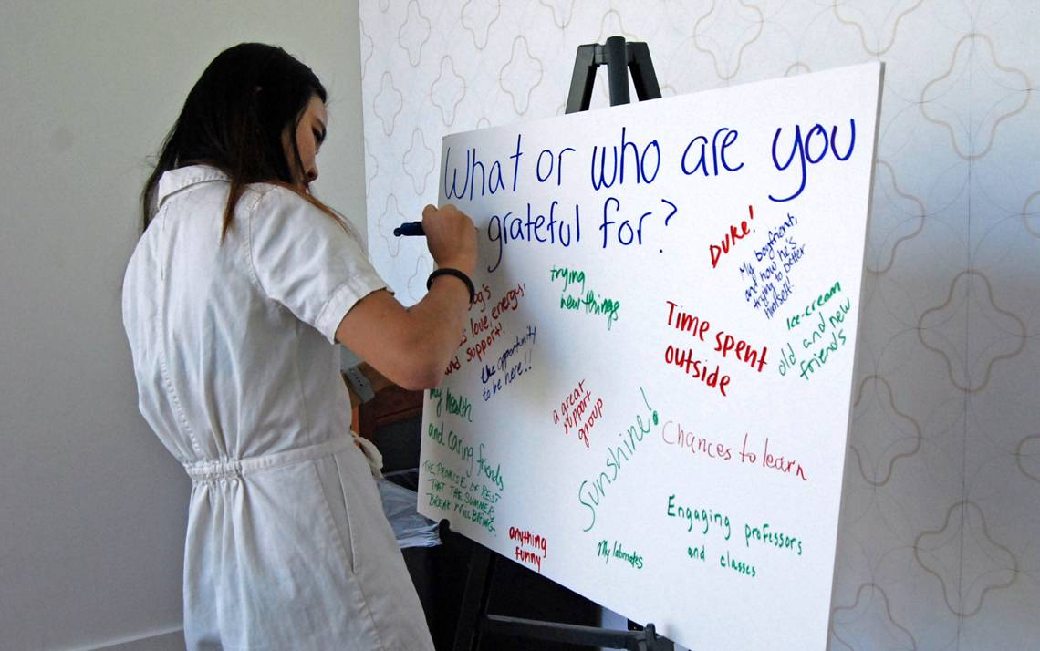 A student writes what she's thankful for during April's Gratitude Lunch, which was organized by Sustainable Duke.