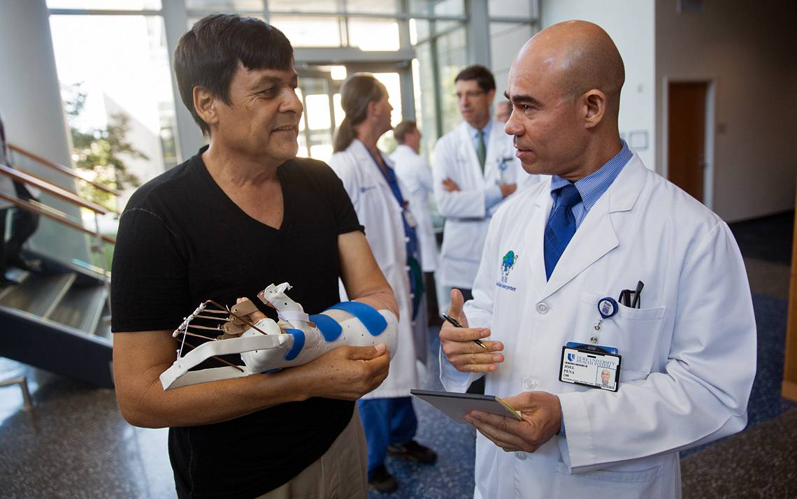 Duke Medical Interpreter Joel Pena, right, talks with hand transplant patient Rene Chavez. Photo by Shawn Rocco, Duke Health.