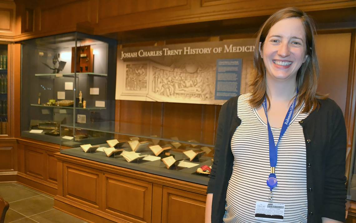 Kate Collins stands in front of the Josiah Charles Trent History of Medicine Exhibit in the David M. Rubenstein Rare Book and Manuscript Library.