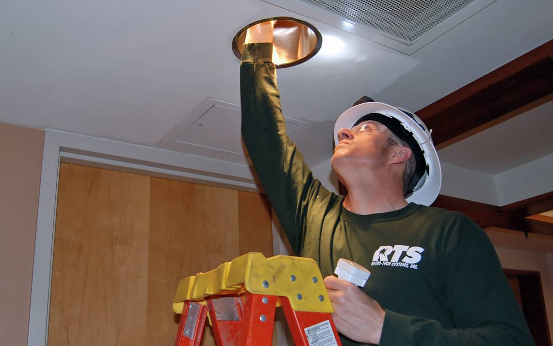 Installer Ryan Roberson puts LED lights into fixtures in Sanford Hall.