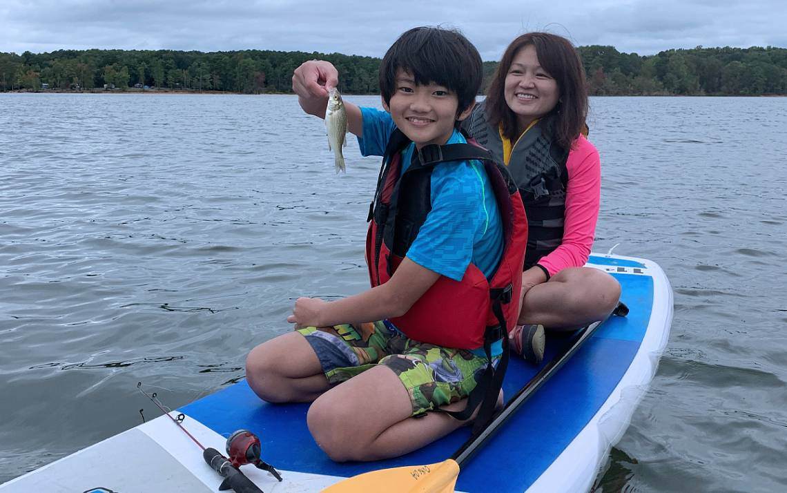 Linda Chang and her son, Jesse, fish on a stand-up paddleboard on Jordan Lake. Photo courtesy of Linda Chang.