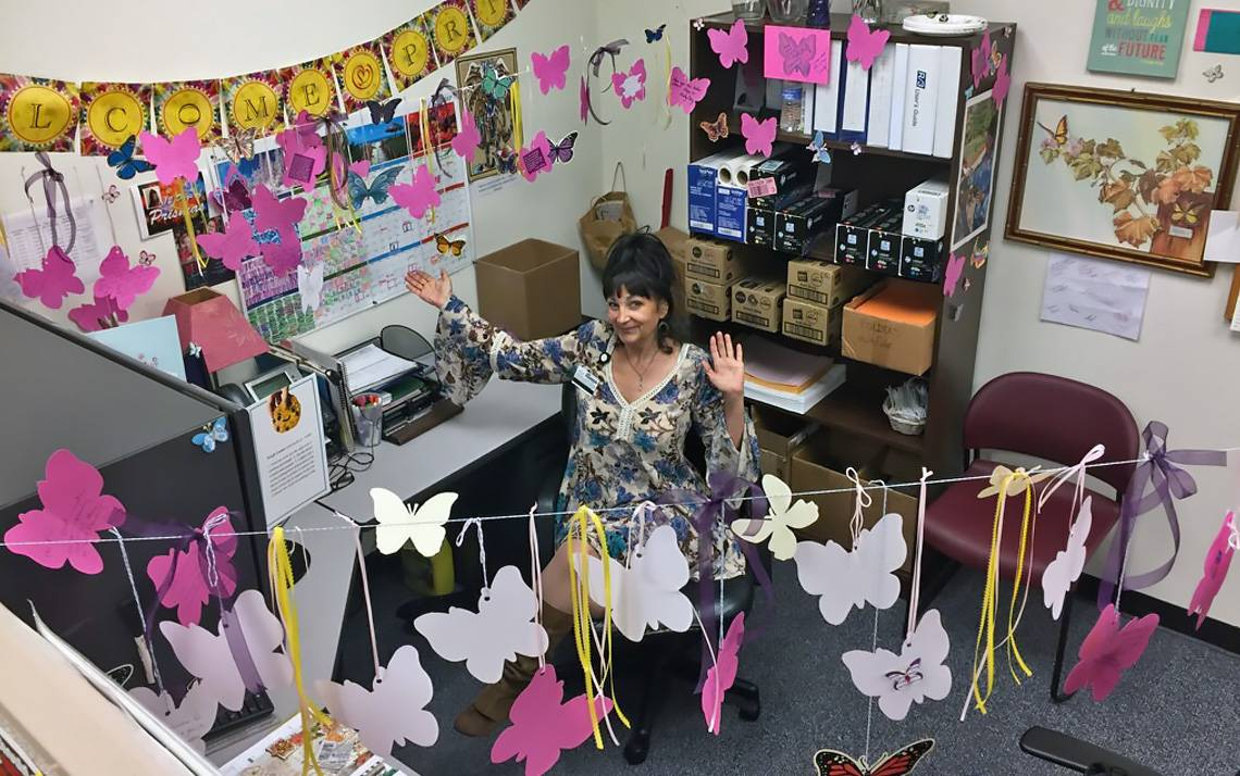 The Office of Communication Services' Pris Toms sits in her cubicle, which was decorated with butterflies by her co-workers.