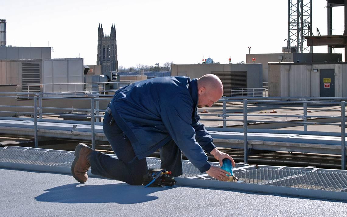 Electrician Bob Moffett repairs a light on top of Duke University Hospital. Photo by Stephen Schramm.